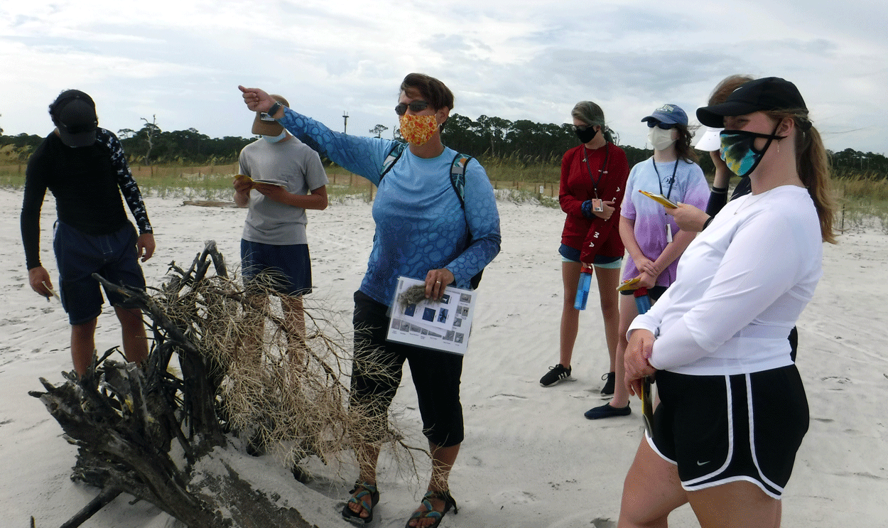 Discovery Hall Programs marine educator points towards the Gulf during high school marine science class.